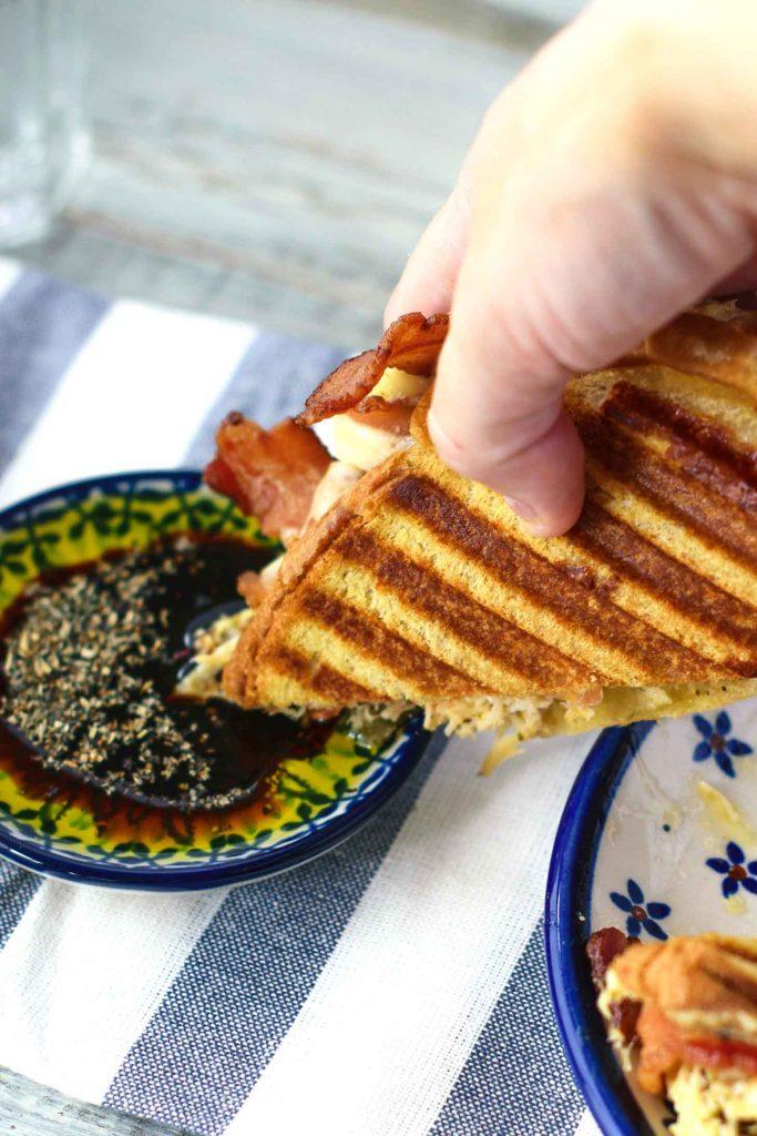 Dip a chicken pesto panini in balsamic vinegar