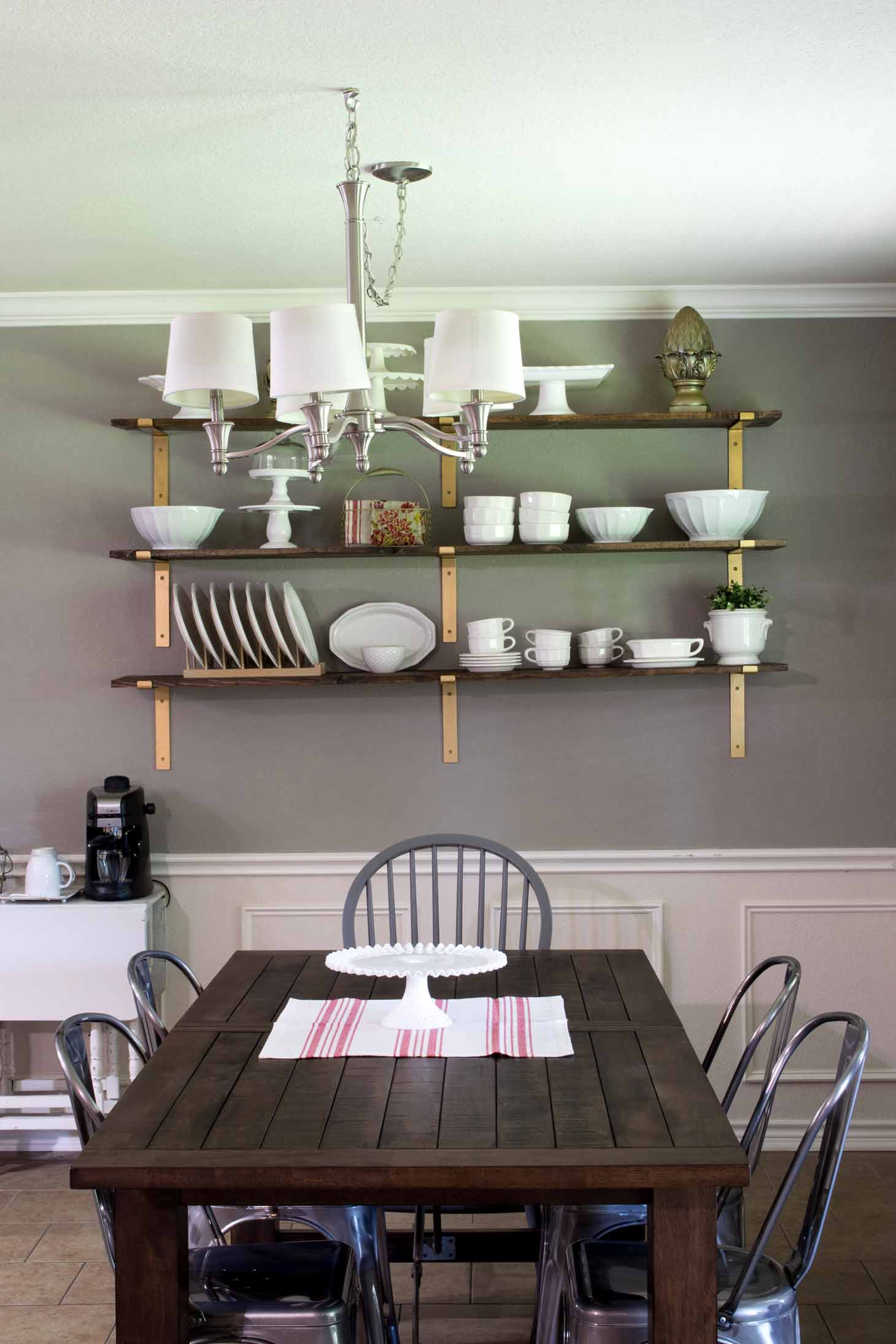 a breakfast room in farmhouse style with open shelves, a rustic table, galvanized chairs, and a coffee area