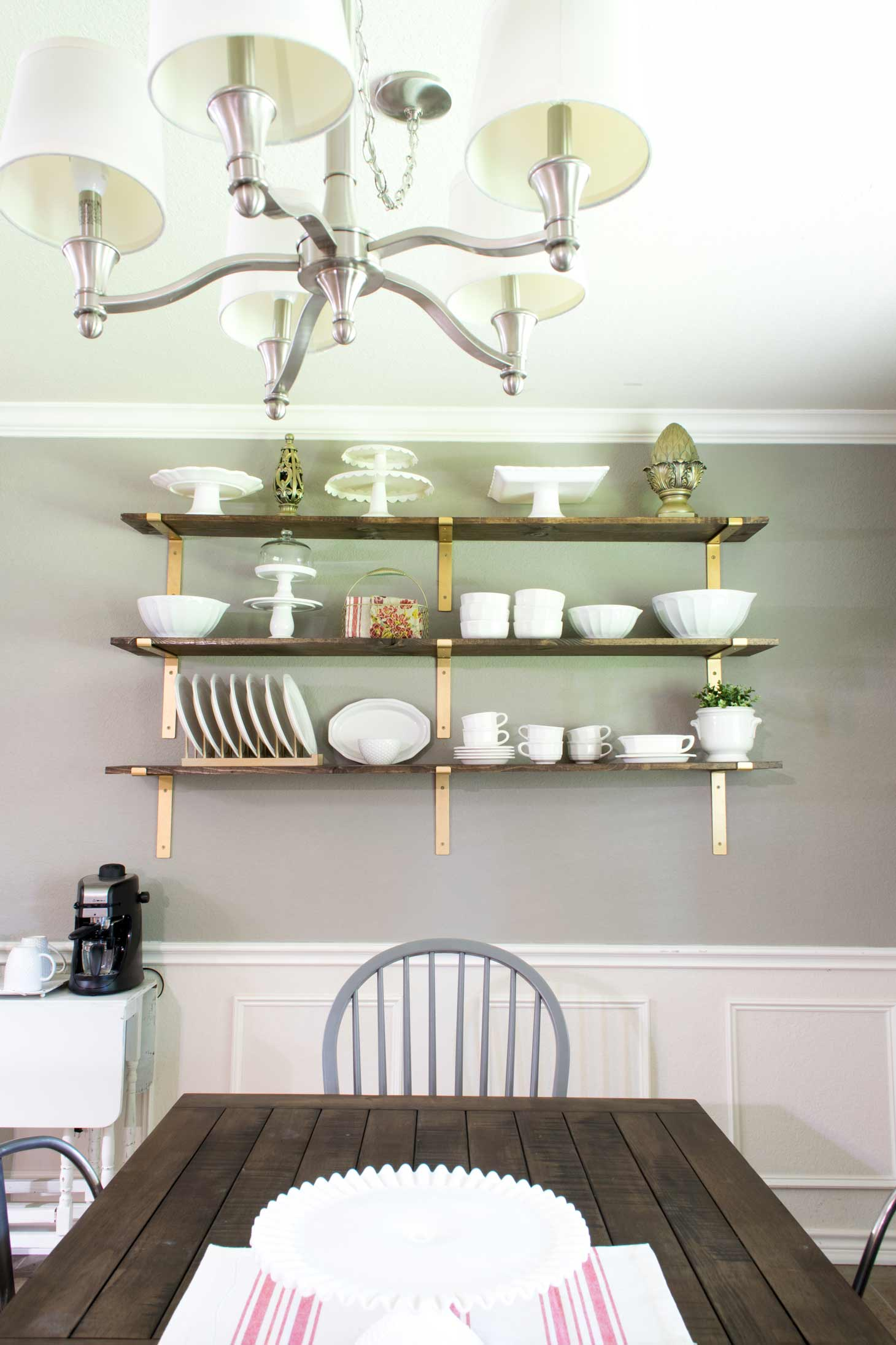 A rustic wood table with open shelving on a wall for the farm house look