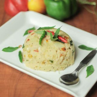 Suji upma on a white plate with dark background and some bell peppers