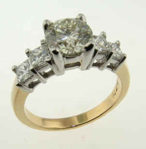 Round diamond accented by stepped princess cuts.