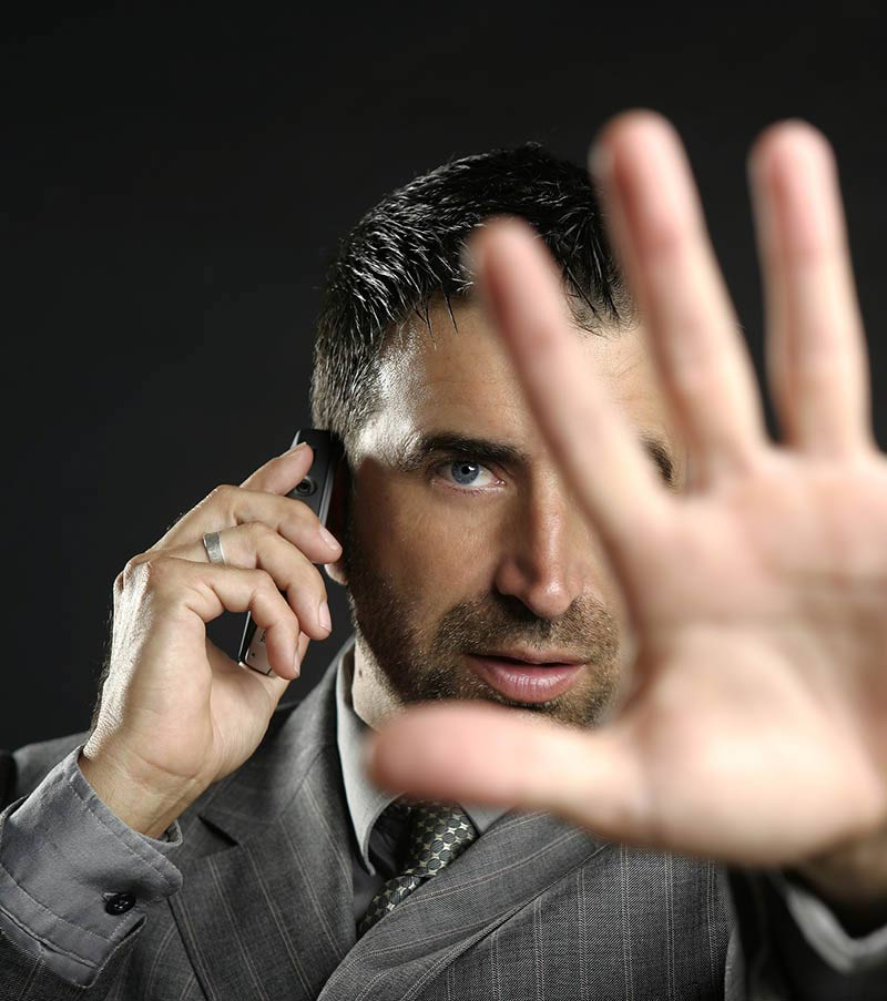 Angry businessman saying stop with hand,talking to a mobile phon