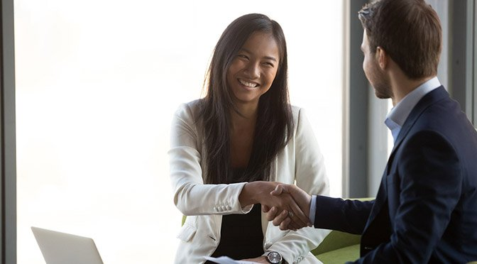 Businessman handshake smiling Asian client closing business deal