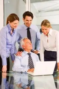 young team members arround old man in office