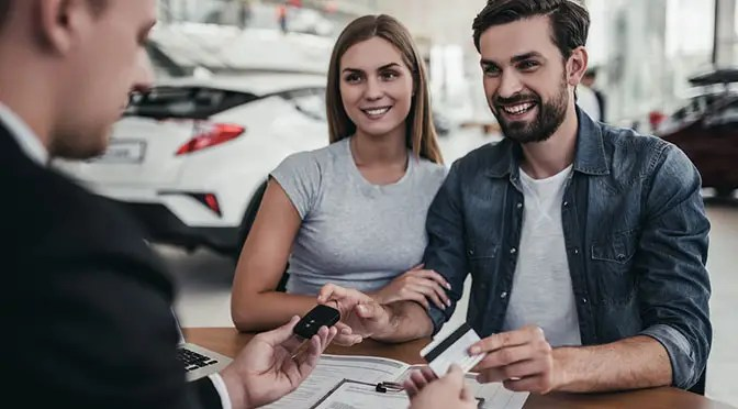 Happy beautiful couple is buying a new car at dealership