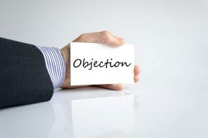 Businessman holding objection card