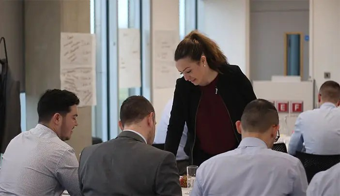Sales trainer working with delegates on a task