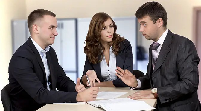 Business negotiations Group of three business people, male and female, discussing the deal. Office interior, serious, authentic emotions