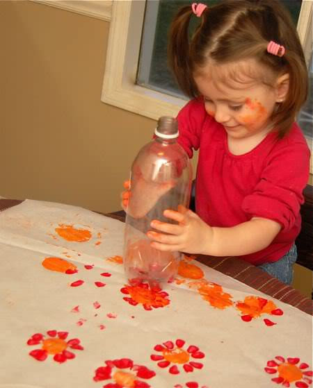 recycled art project of flowers made with bottom of 2L bottle.