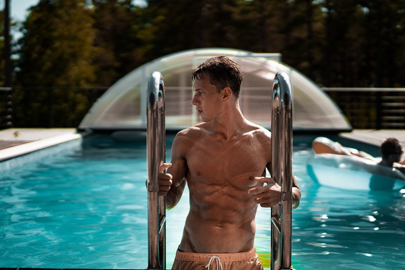 Love Handle Workouts Shirtless Man Getting Out of a Pool