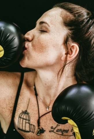 Funny Workout Quotes for Women A Woman Wearing Boxing Gloves Kissing the End of One of the Gloves