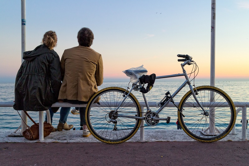 Herbalife Stress Management Products A Couple Sitting on a Bench Next to a Bike Overlooking the Ocean