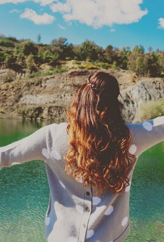 Herbalife Stress Management Product Benefits Woman Standing in Front of a Lake with Her Hands in the Air