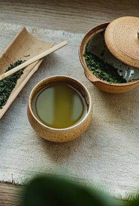 Metabolism Boosting Tea Recipes Overhead View of a Cup of Green Tea with Ingredients Nearby