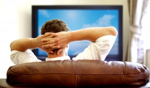 Man sits on couch watching tv