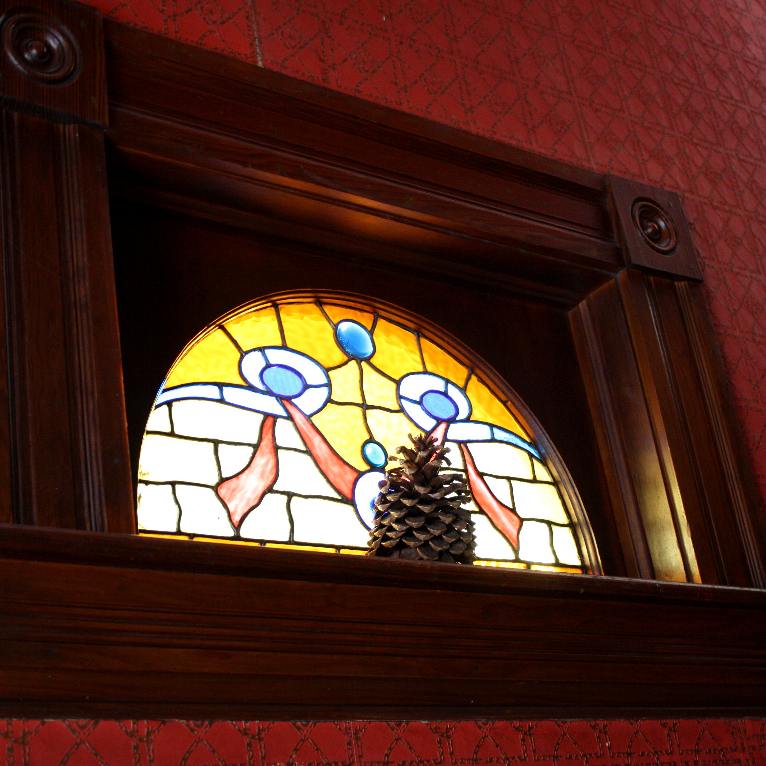 Half Circle Stained Glass Window With Pinecone On Sill