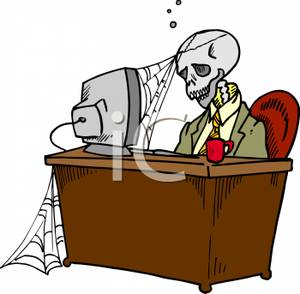 A Skeleton Sitting At An Office Desk Royalty Free