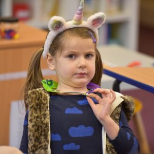 A child wearing a Unicorn headband.