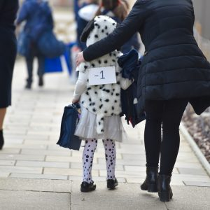 A small school child dressed as a Dalmatian walking on a pavement with her mother.