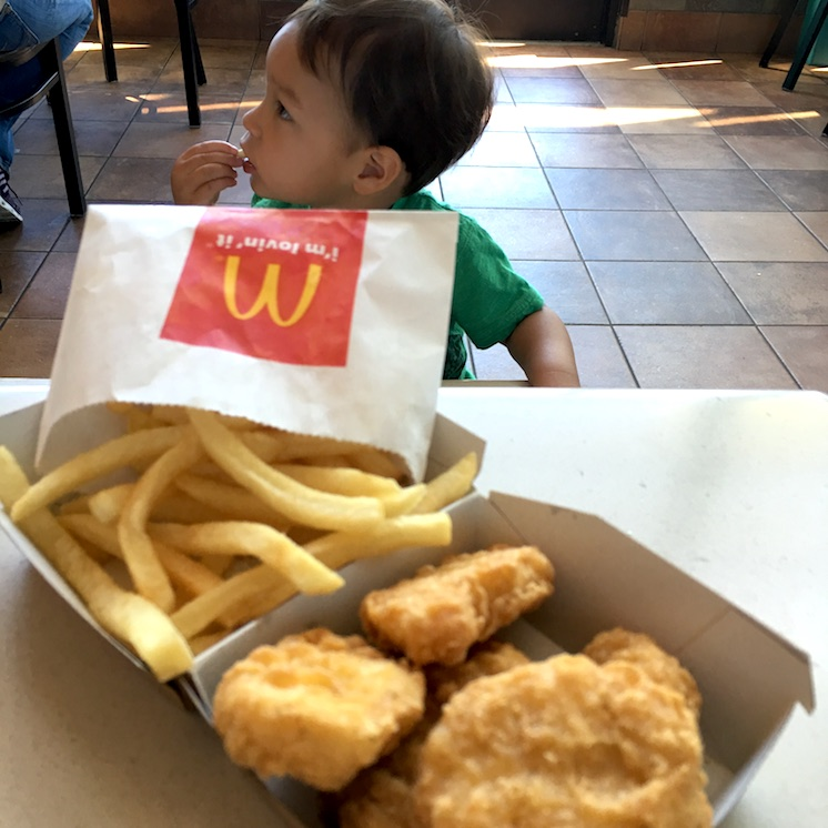 Cute baby eating chicken nuggets at McDonald's