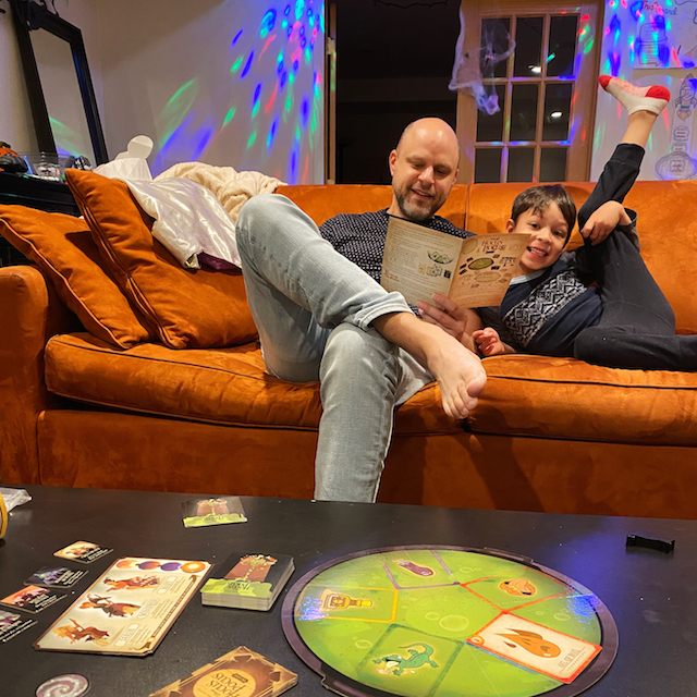 man and son on couch playing hocus pocus board game