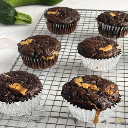 Chocolate zucchini muffins with peanut butter on cooling rack with zucchini