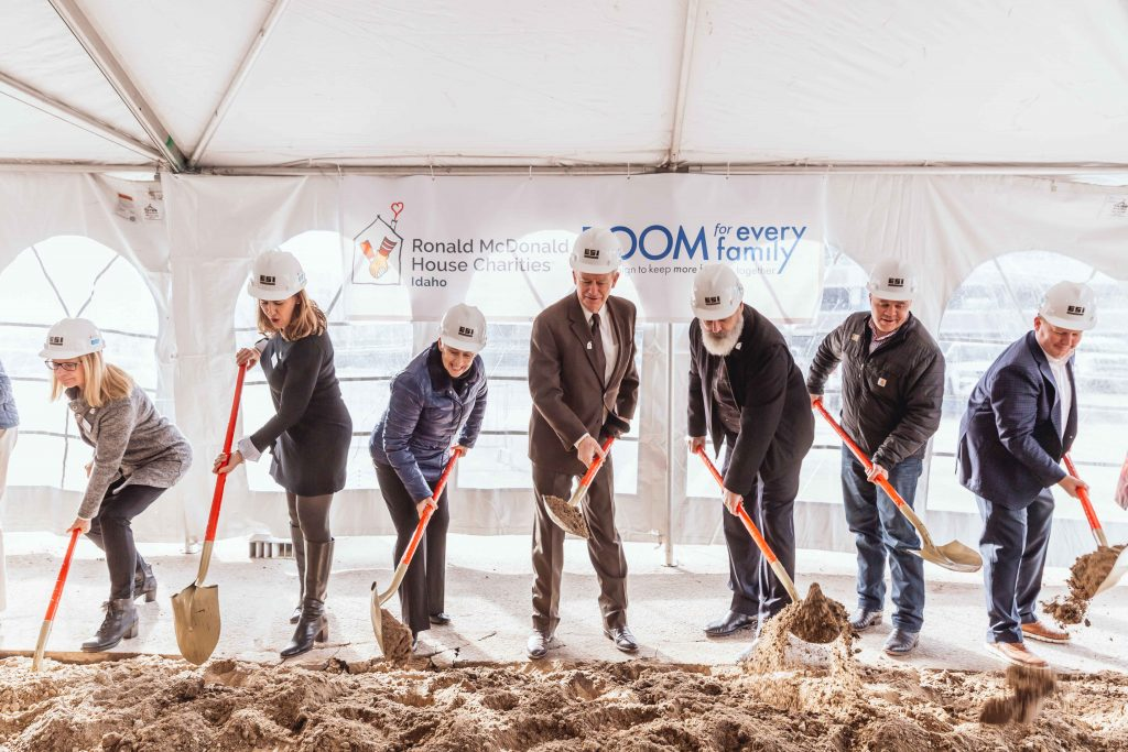RMHC of Idaho leadership and supporters wearing hard hats and using shovels to break ground on a new Ronald McDonald House in Boise.