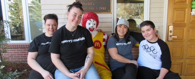 Merry Maid employees pose for the camera in front of the Ronald Mcdonald House.