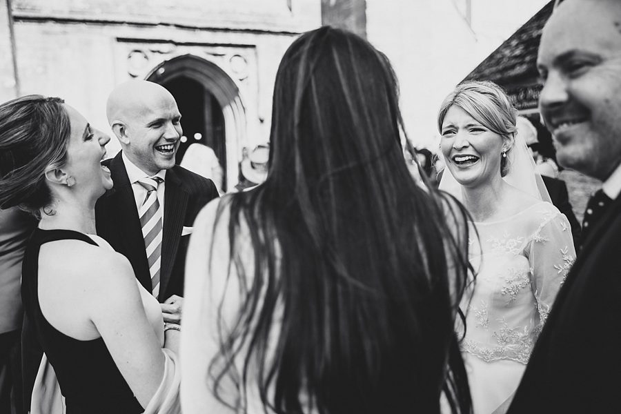 bride laughing outside cirencester church by sam gibson