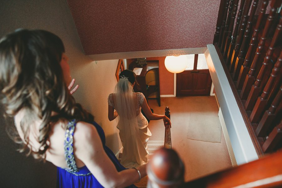bride going downstairs in her wedding dress at home
