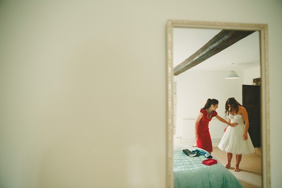 bride adjusting her wedding dress at home