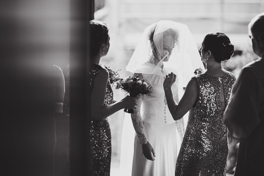 bride adjusting veil at the church door before a wedding