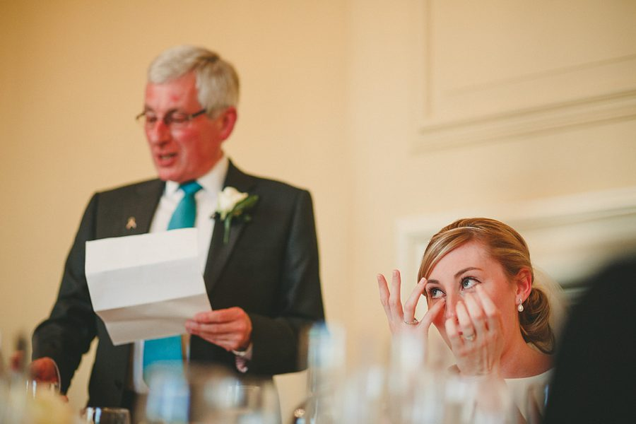 groom laughs during speech at a wedding at kingscote barn