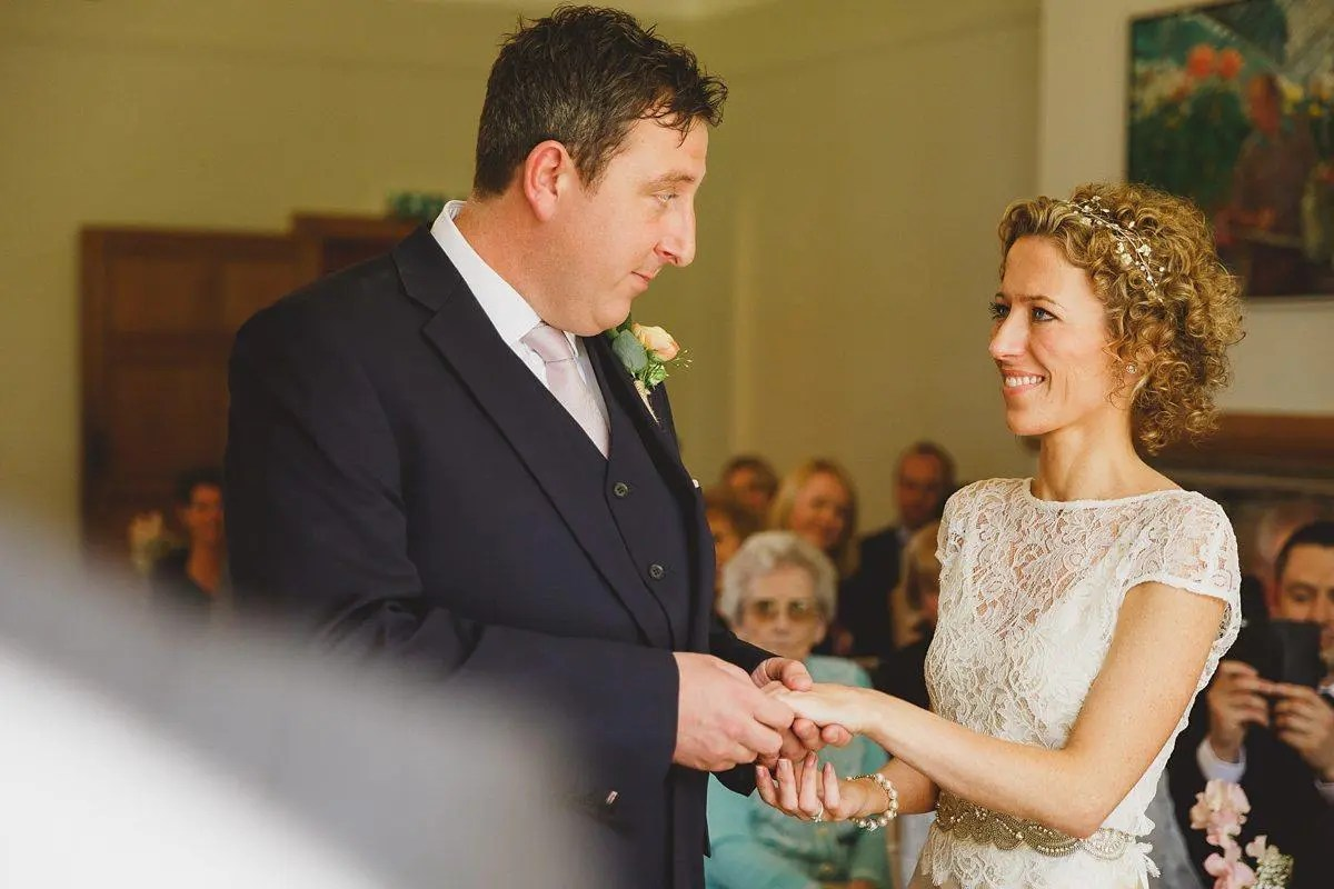 bride and groom exchanging rings at coombe lodge