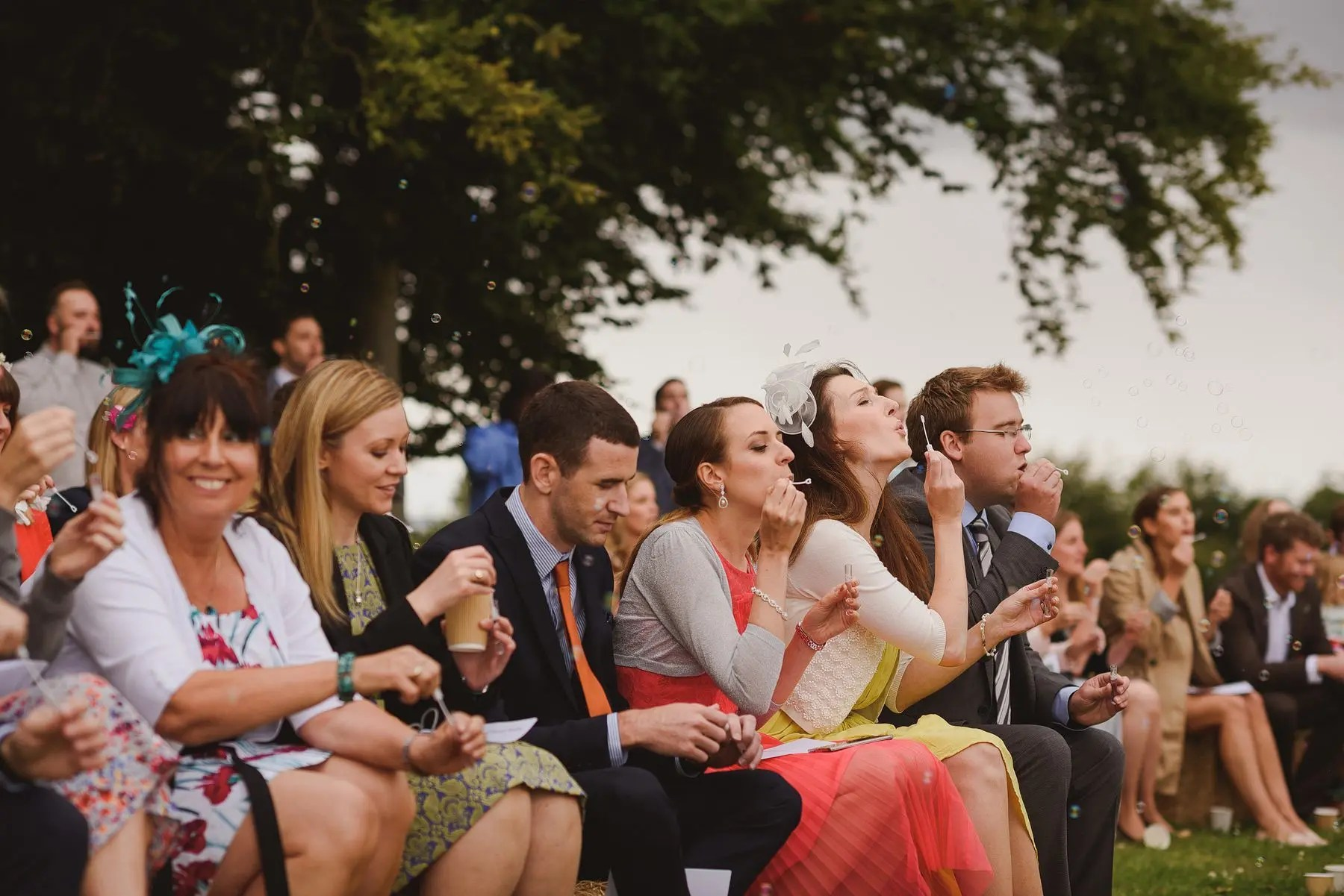 guests blowing bubbles during wedding ceremony