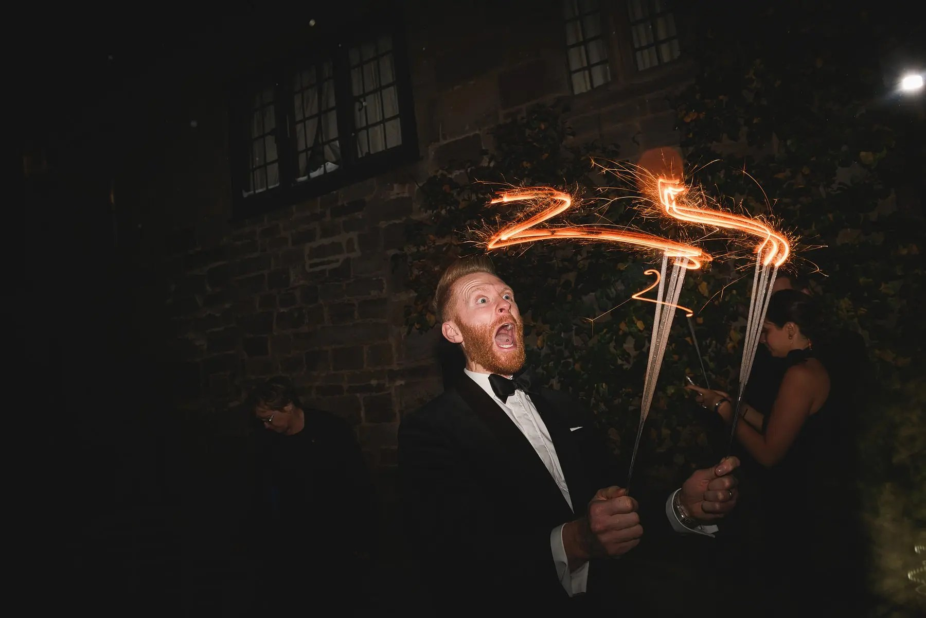 funny groom with sparklers