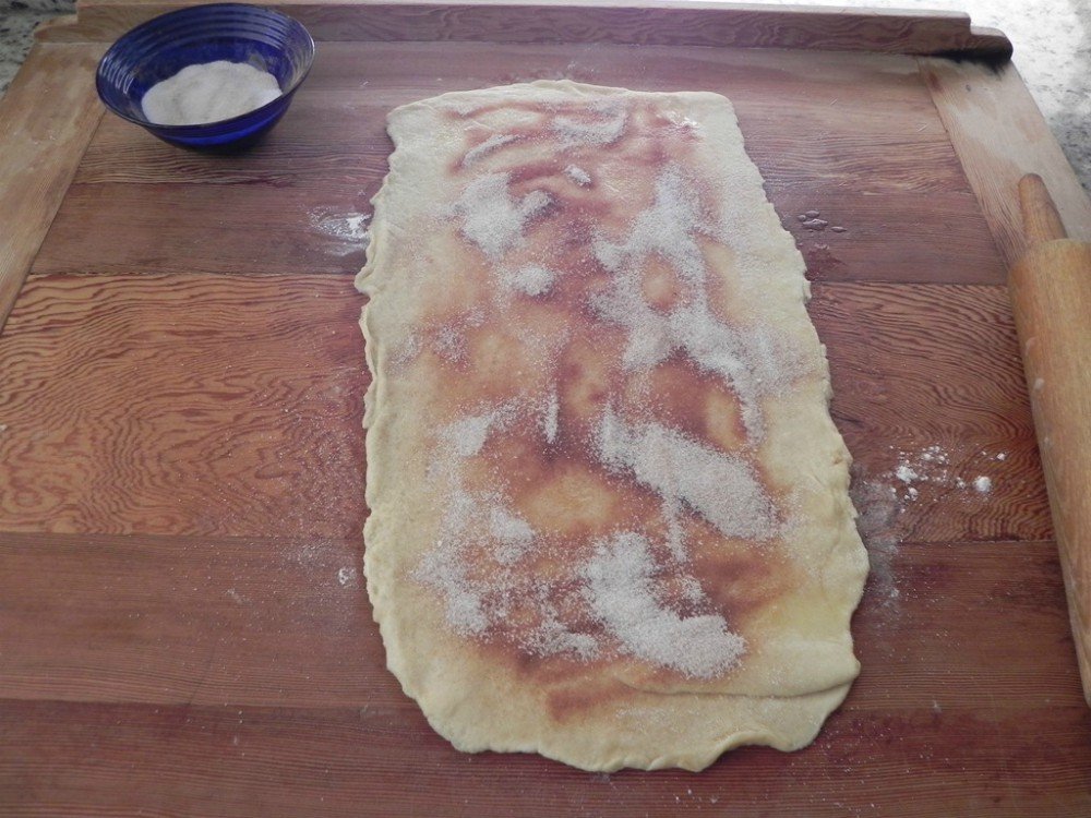 overhead image of cinnamon sugar on rolled out dough