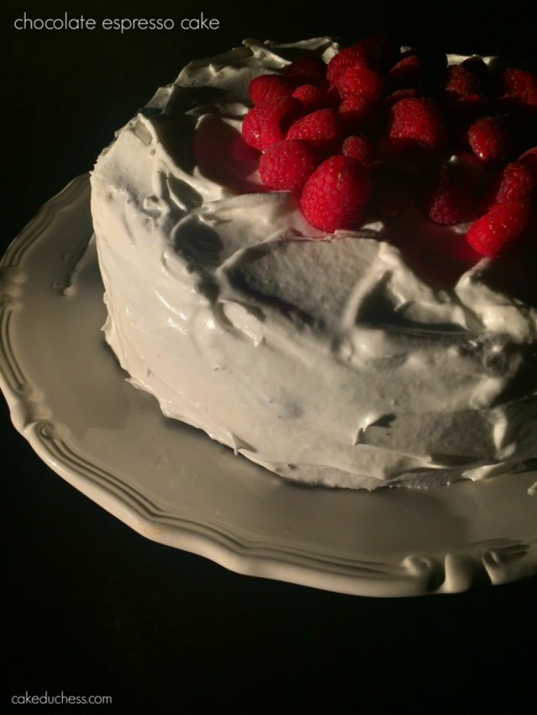 image of a cake with berries on top on a white cake plate