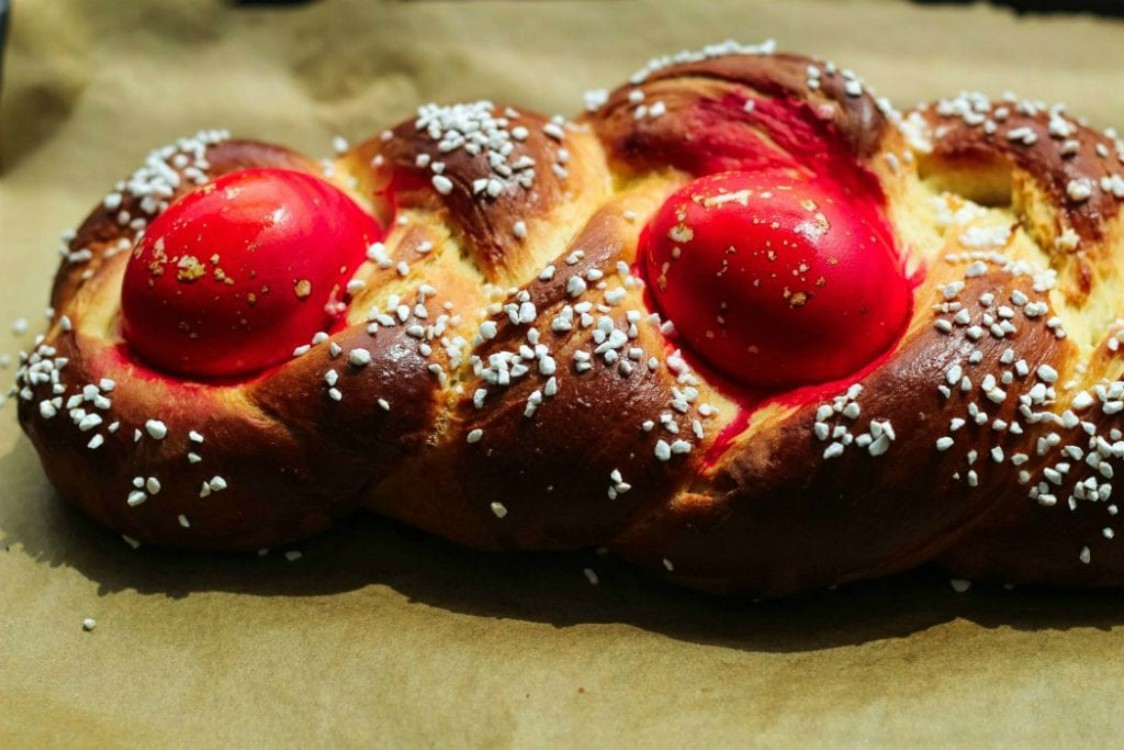 overhead image of loaf of easter sweet bread with red eggs