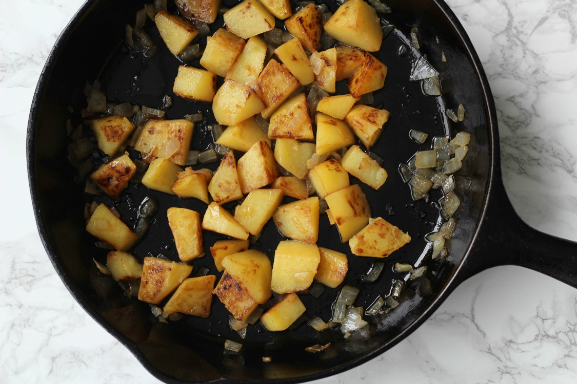 overhead image of potaotes and onions in a skillet