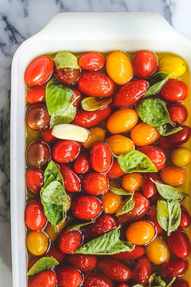 overhead image of cherry tomatoes in olive oil and basil in a casserole