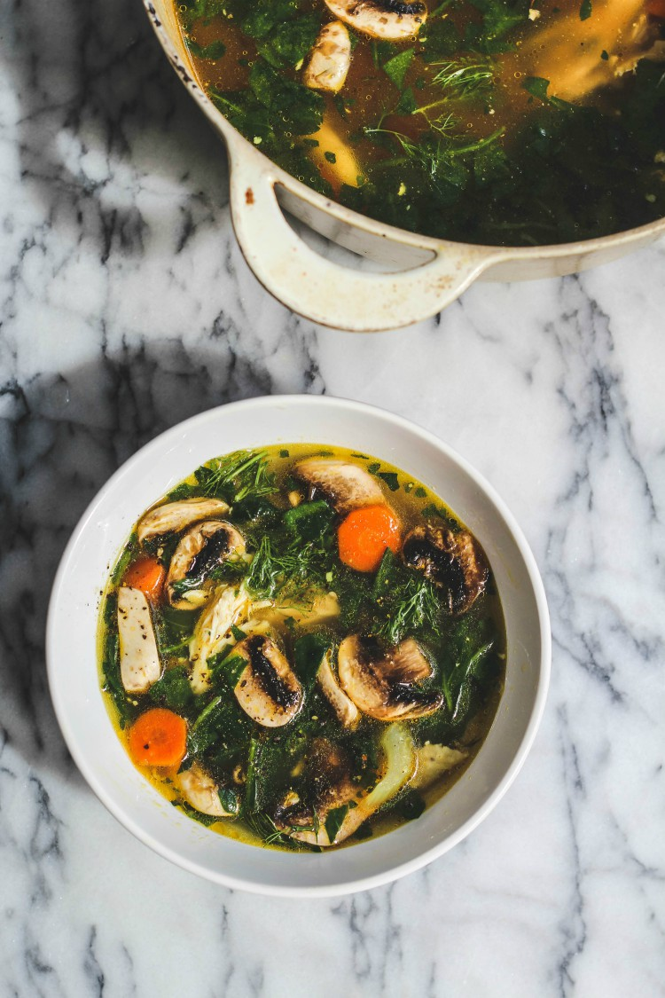 overhead image of mushroom vegetable soup in a white bowl on marble background