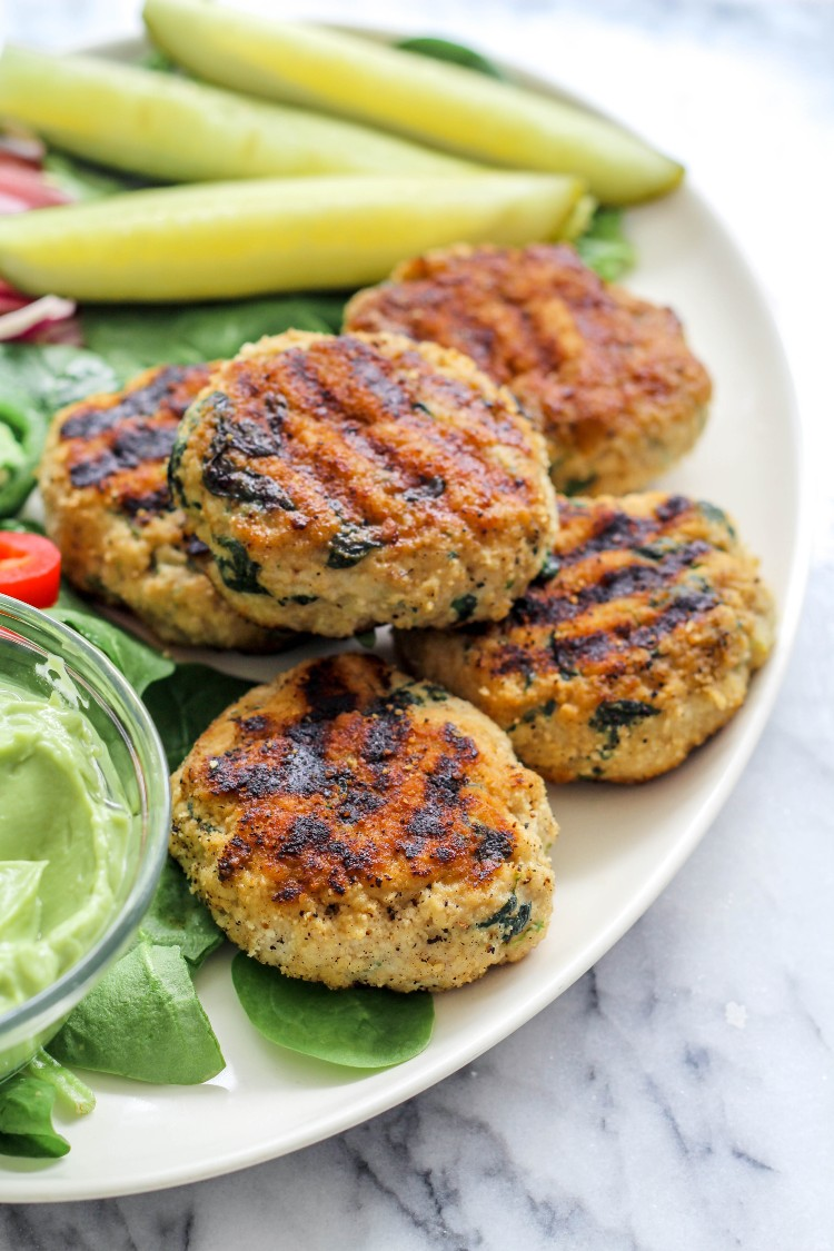 overhead image of spinach chicken burgers on a white plate