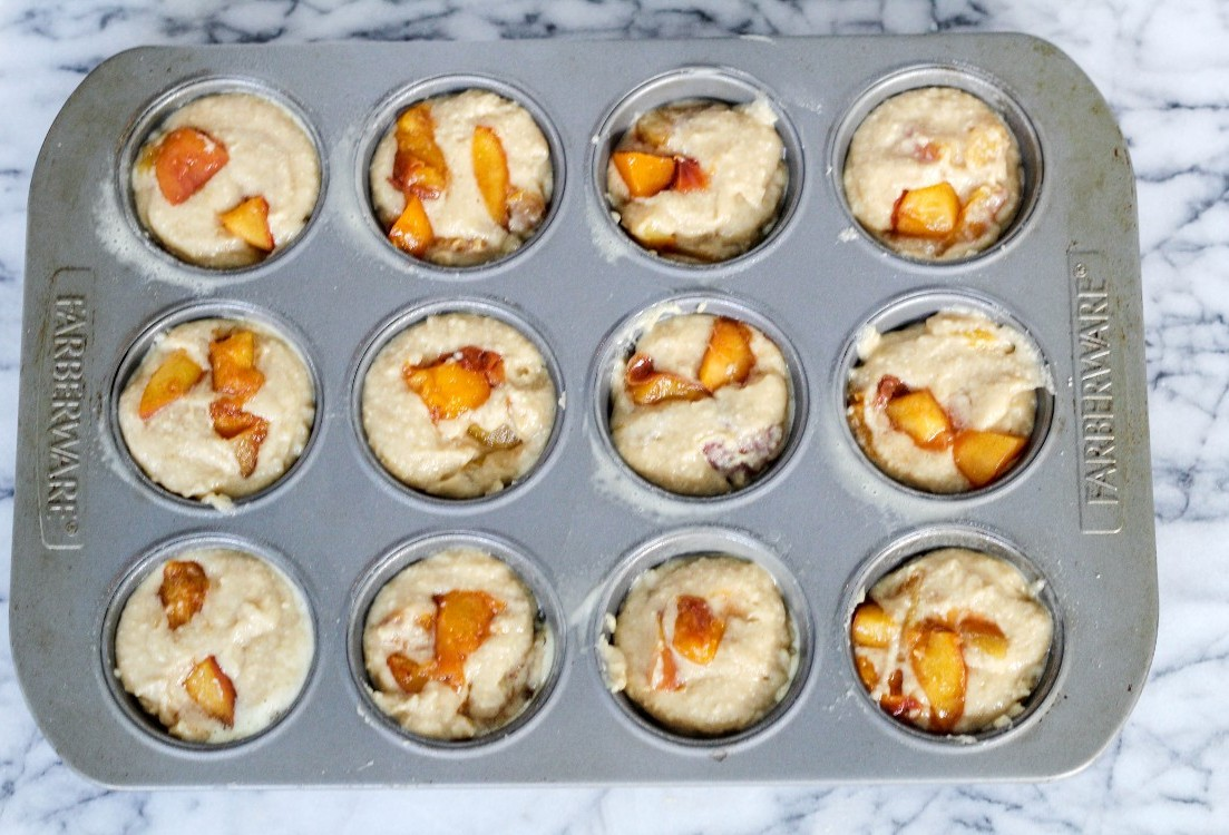 overhead image of peach muffins in baking tin