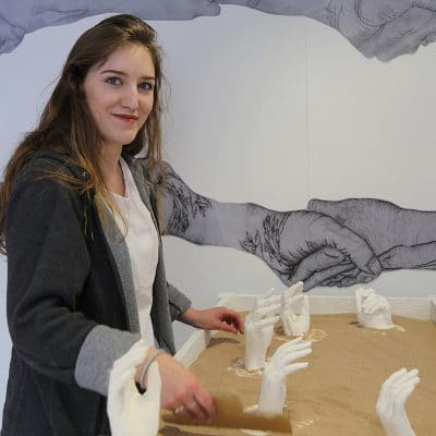 A girl holding a sculpture she created in sand