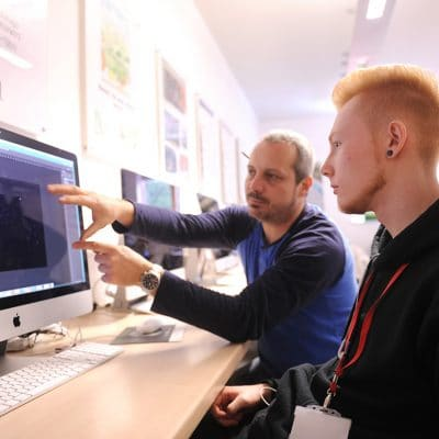 a teacher pointing at a screen with a graphic design student in front