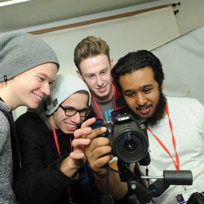 photography students looking at a camera