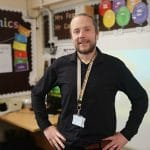 Liam Carr stands in his classroom hands on hips