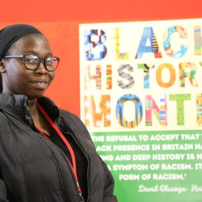 Student Fatima in front of a poster for Black History Month