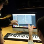 Music production students work collaboratively around computer display.